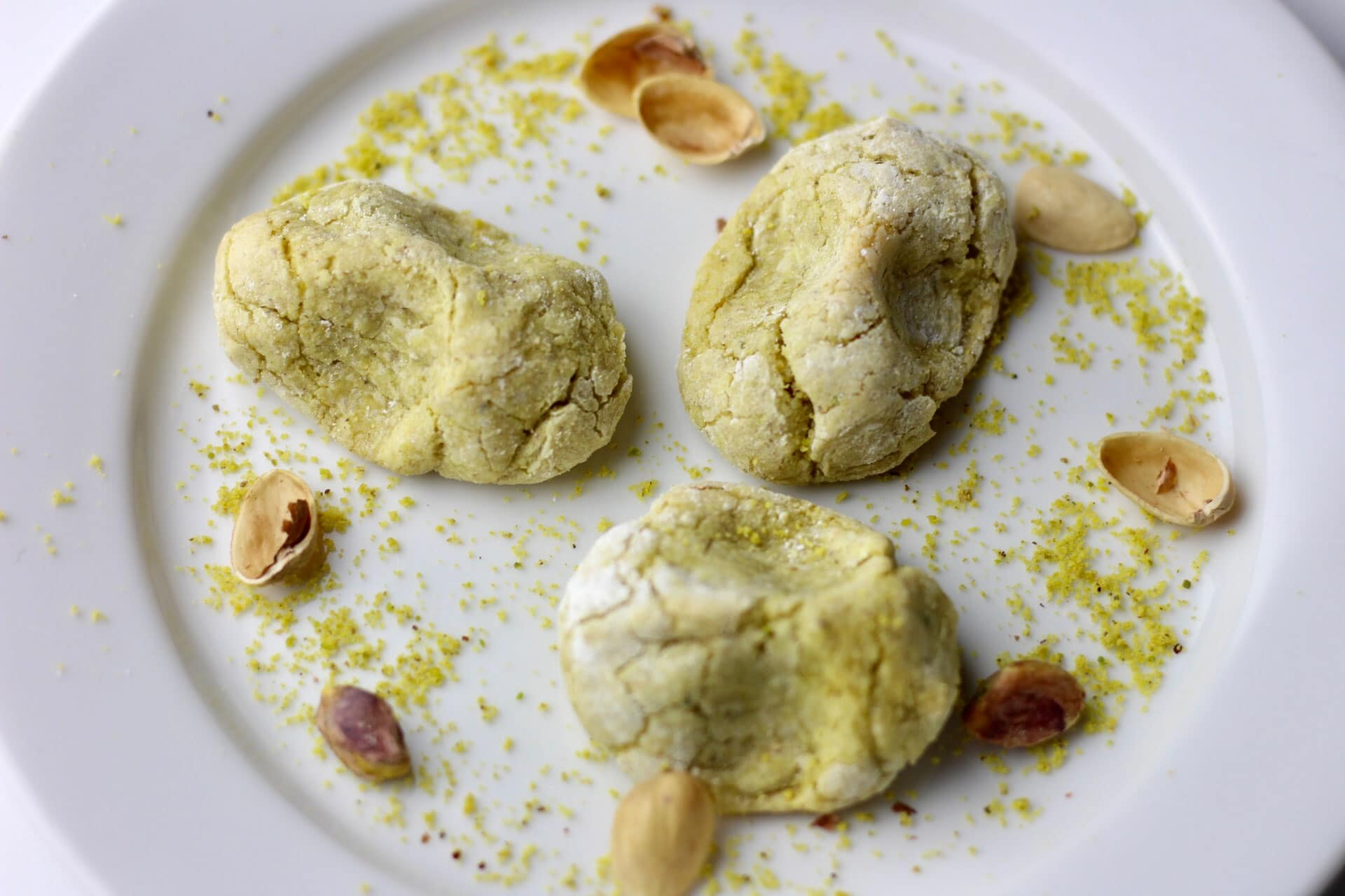 Three pistachio cookies served on a plate with pistachio shells for decoration.