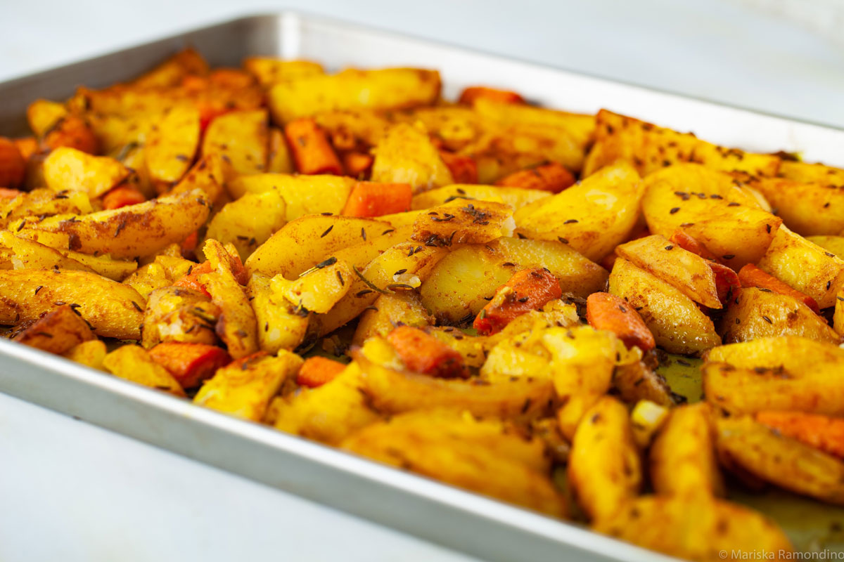 Oven-baked Potatoes with Jamaican Curry and Caraway Fruits in oven tray