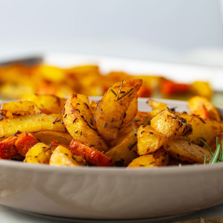 Oven-baked Potatoes with Jamaican Curry and Caraway Fruits in a plate