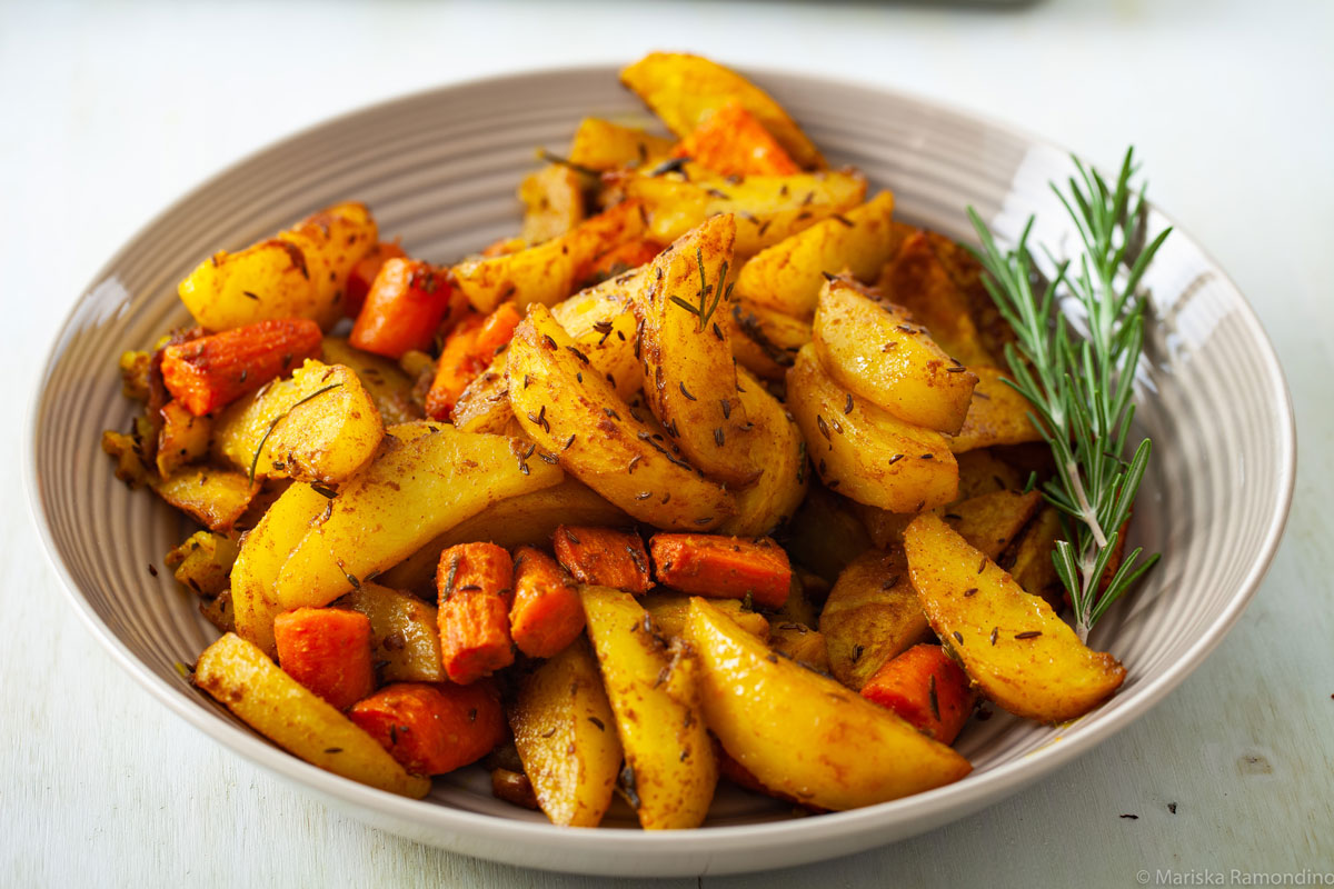 Oven-baked Potatoes with Jamaican Curry and Caraway Fruits with Rosemary for Garnish