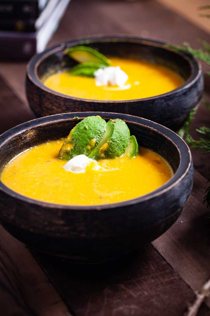 Two bowls of Red Kuri Squash Soup topped with avocado and a spoon of coconut cream