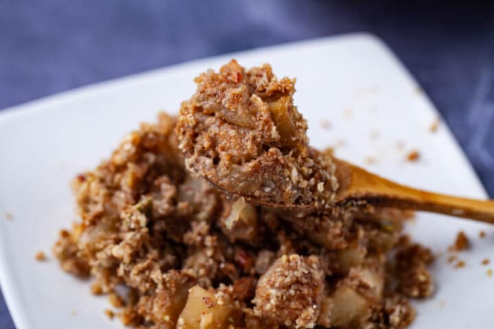 A wooden spoon filled with grain-free apple crisp resting on top of a bed of the same healthy apple dessert on a small plate.