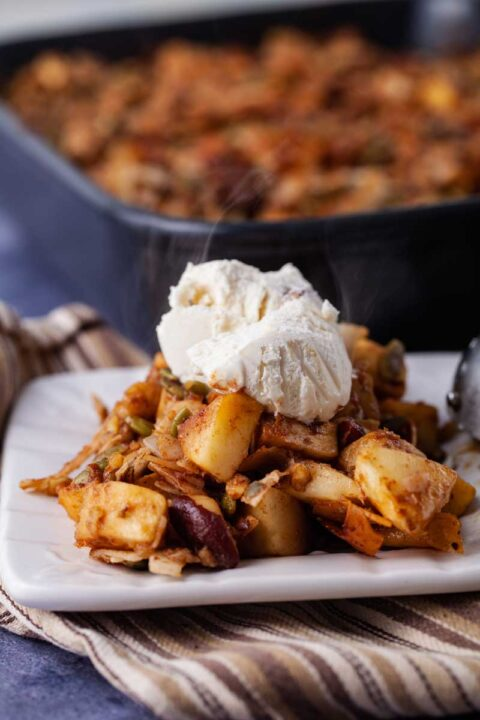 Warm apple crisp on a small plate topped with a scoop of Keto ice cream.