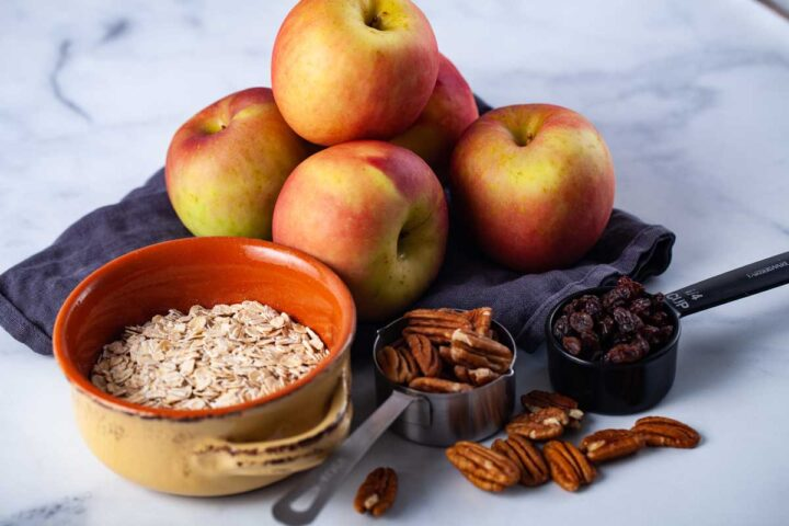 Red apples on a blue kitchen towel, a bowl of uncooked oatmeal, a fourth cup of dark raisins, and a third cup of half pecan nuts laid out on a table.