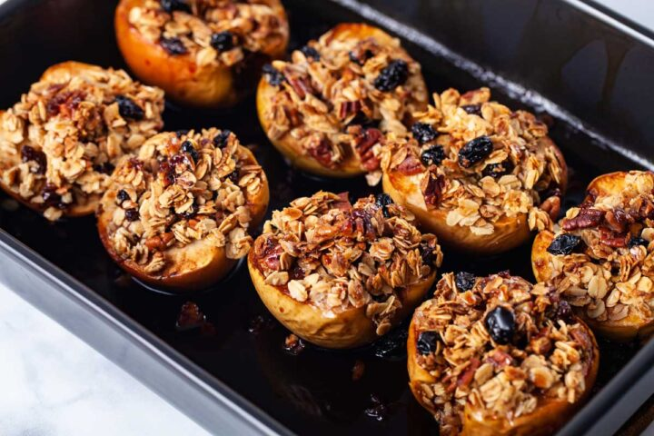 A baking dish containing stuffed and syrupy apples.