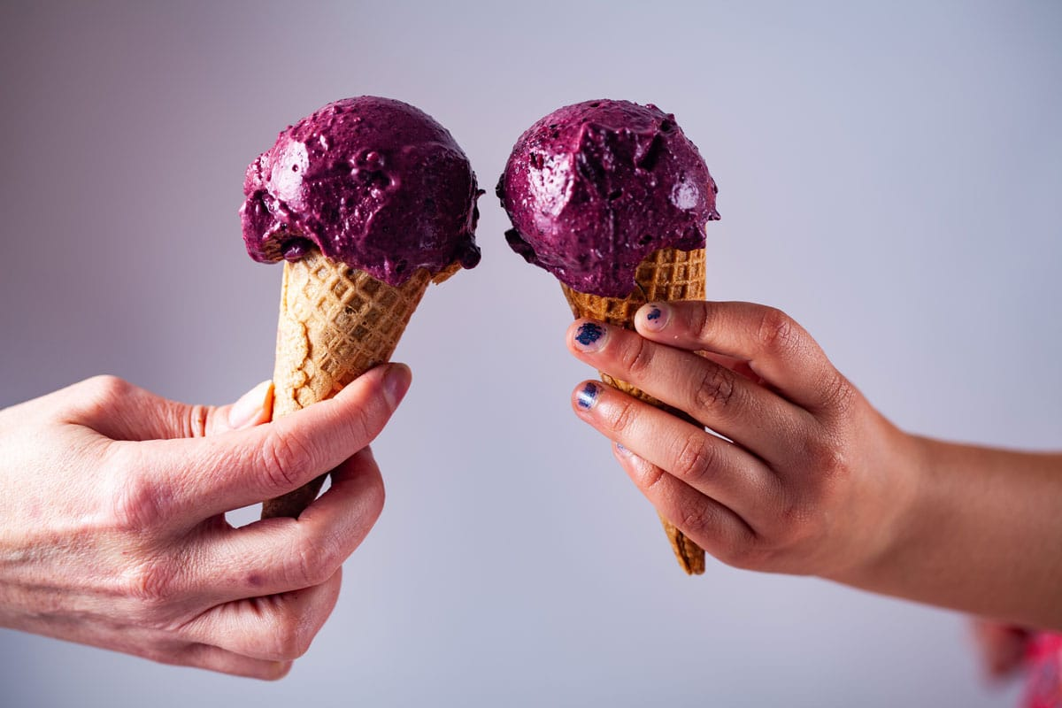 Two hands carrying each a berry ice cream on a cone.