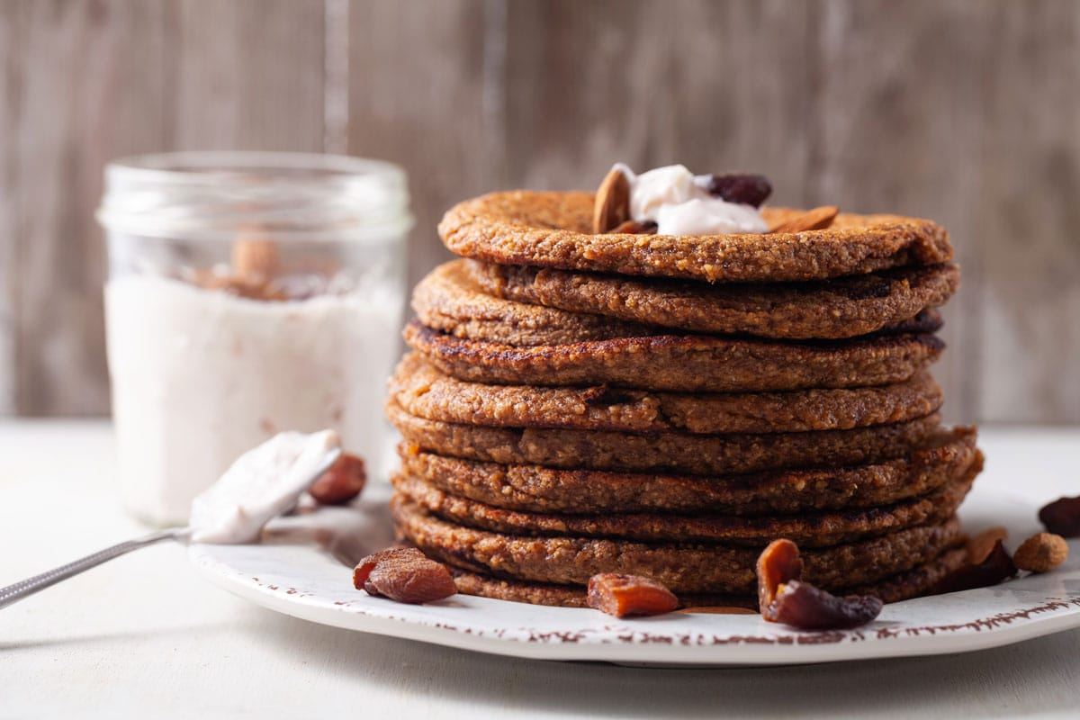 A STACK OF OAT FLOUR PANCAKES WITH NUTS AND APRICOTS TOPPINGS