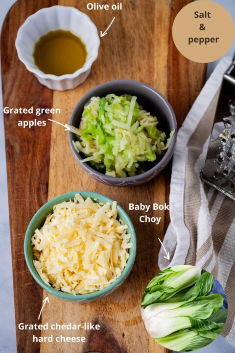 Ingredients such as olive oil, grated green apples, baby bok choy, grated Chedar-like cheese, and salt and pepper to make a roasted baby bok choy recipe.