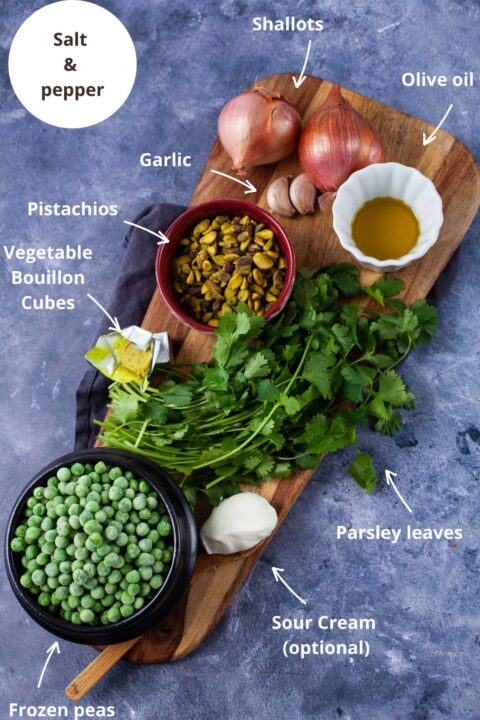 Ingredients such as salt and pepper, shallots, olive oil, garlic, pistachios, vegetable bouillon cubes, fresh parsley leaves, sour cream, and frozen peas to make soup.