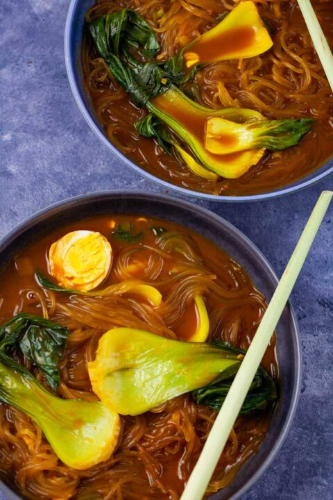 Two bowls filled with bok choy noodle soup topped with half of a cooked egg.