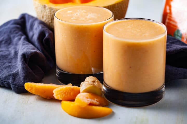 Two glasses of cantaloupe smoothies shown amongst a few ingredients like half a cantaloupe, more frozen peaches, and ginger.