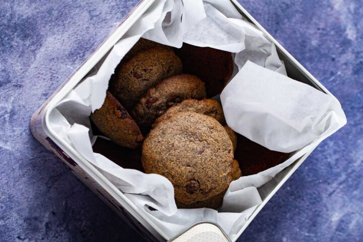 Buckwheat chocolate chip cookies stacked in a tin cookie box.