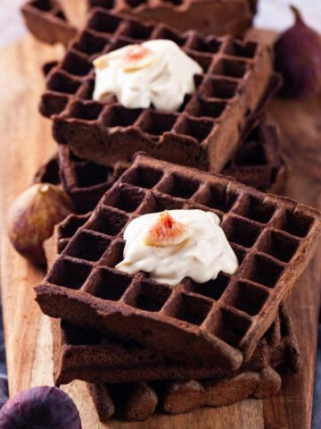 Stacks of buckwheat waffles arranged on a wooden board, topped with yogurt and figs.