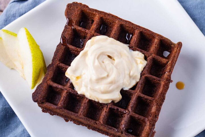 One golden brown waffle served on a white plate, topped with coconut yogurt and served with slices of pears and a drizzle of maple syrup.