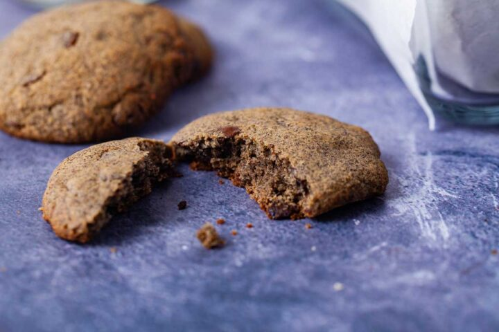 A close up of a chocolate chip cookie broken in two.