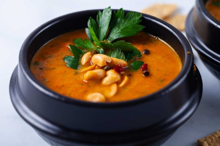 A closeup of a black bowl filled with orange carrot soup, topped with roasted peanuts, chili, and fresh Parsley leaves.
