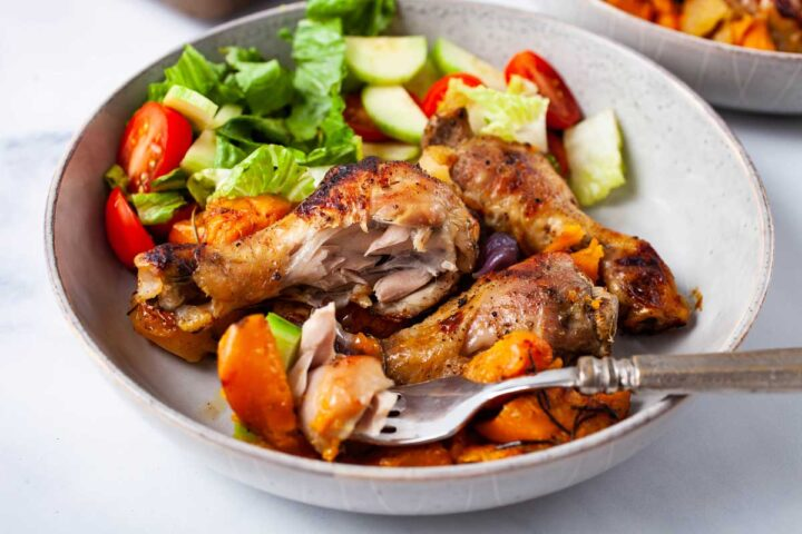 A fork resting on a plate filled with roasted drumsticks, veggies, and a green salad.