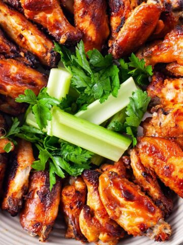 A plate neatly filled with baked chicken wings and garnished with celery and parsley.