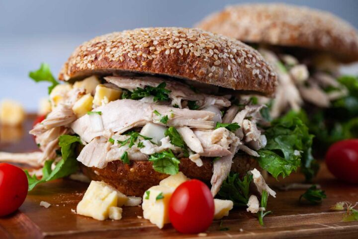 A wooden board topped with two chicken sandwiches and small red tomatoes and cubed hard cheese randomly spread on the side.