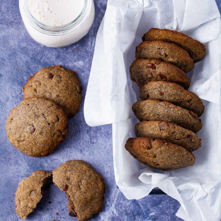 A basket filled with buttery buckwheat cookies, next to a cup of milk and some cookies spread out on the table.