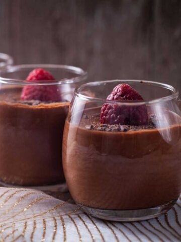 Mini glasses filled with chocolate mousse and topped with a fresh raspberry and shaved chocolate pieces.