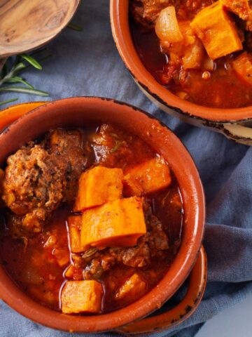 Two terracotta bowls filled with a meat sweet potato and stew.