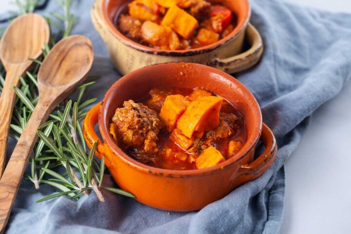 Two terracotta bowls filled with a meat sweet potato and stew, served next to two wooden spoons and fresh Rosemary leaves.