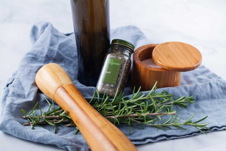A wooden pot filled with salt, dried basil seasoning, a wooden pepper mill, an olive oil bottle, and fresh Rosemary leaves showcased on a blue kitchen towel.