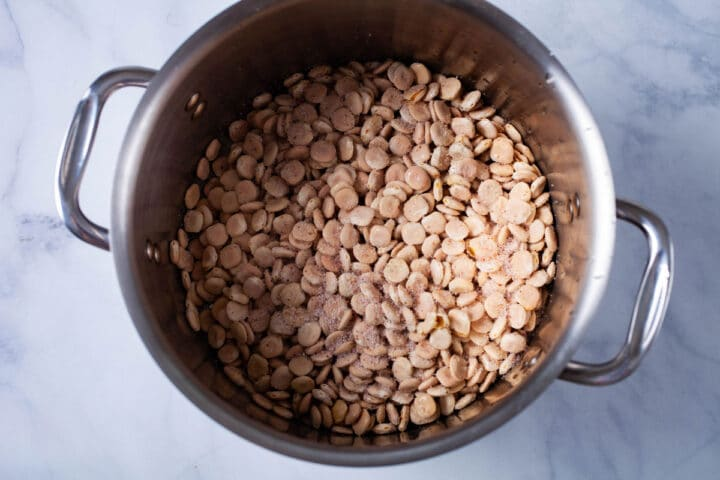 A large pot filled with uncooked Lupini beans and topped with salt.