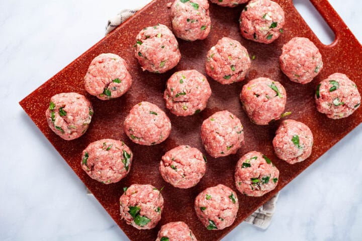 A large cutting board holding a lot of raw and seasoned meat balls.