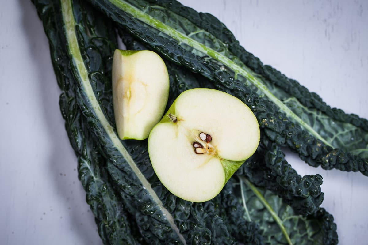 Raw Dinosaur kale with a sliced green apple