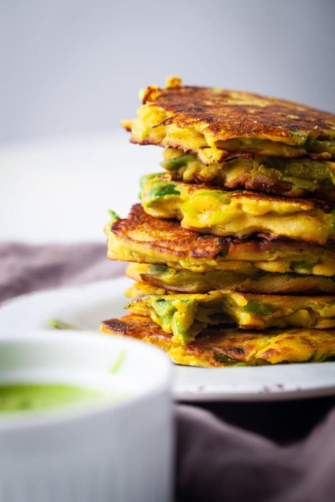 A stack of crispy leek veggie cakes served on a plate with a pesto sauce on the side.