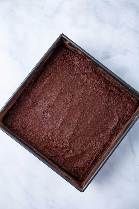 A squared pan containing dark chocolate batter.