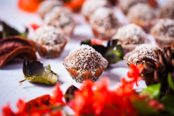 A close-up of energy balls sprinkled with dried coconut flakes and served in tiny paper cupcake holders.