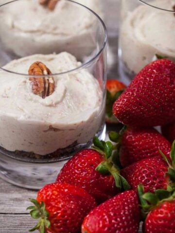 A close up of a glass cup with a layer of crumble and a thick layer of avocado strawberry cream, topped with a pecan nut next to fresh strawberries.