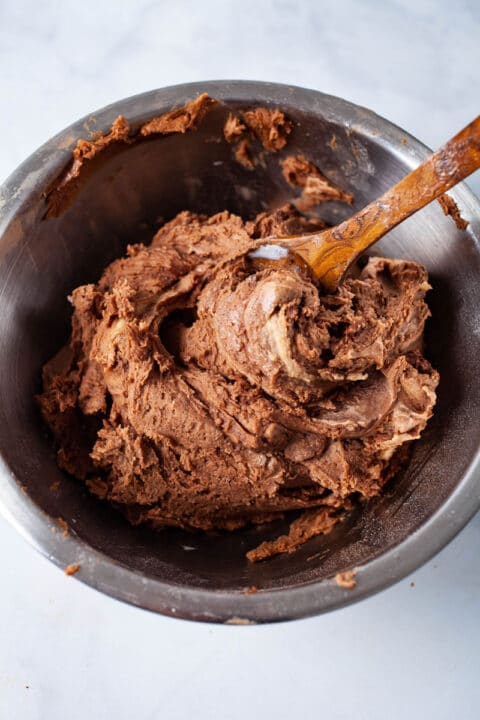 A wooden spoon swirled in chocolate cookie dough.