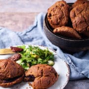 Gluten-free Teff flour biscuits served in a wooden bowl next to a plate with salad and jam filled biscuits.