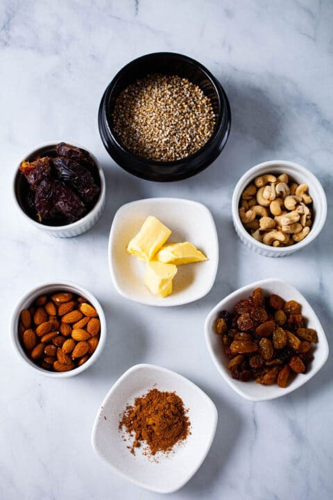 Ingredients like oats, dates, nuts, butter, spices, and raisins spread out on a table.
