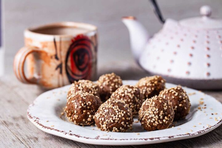 Energy balls sprinkled with seeds served on a small plate next to a cup and Asian teapot.
