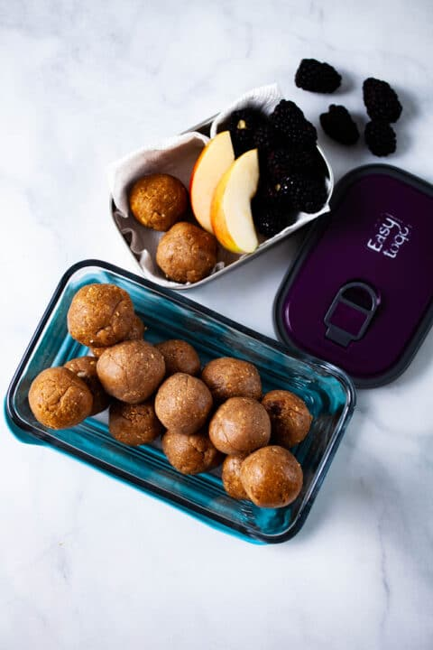 An open container filled with energy balls next to a snack box with two energy bites and fruits.