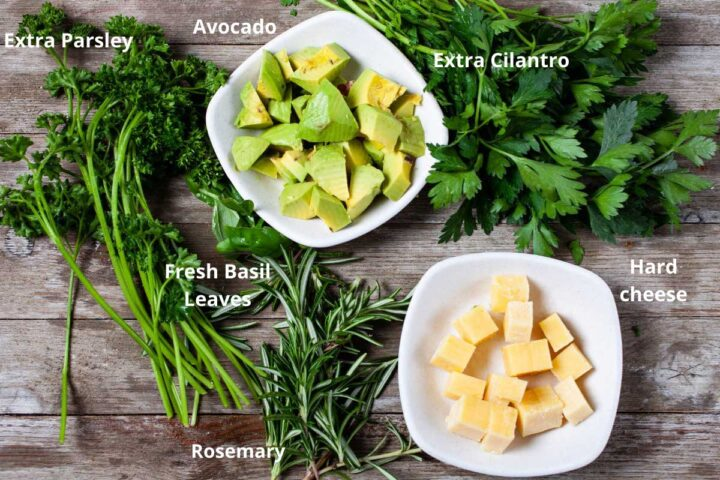 A wooden board with fresh ingredients such as parsley leaves, cubed avocado, cilantro leaves, fresh basil leaves, cubed hard cheese, and sprigs of Rosemary.