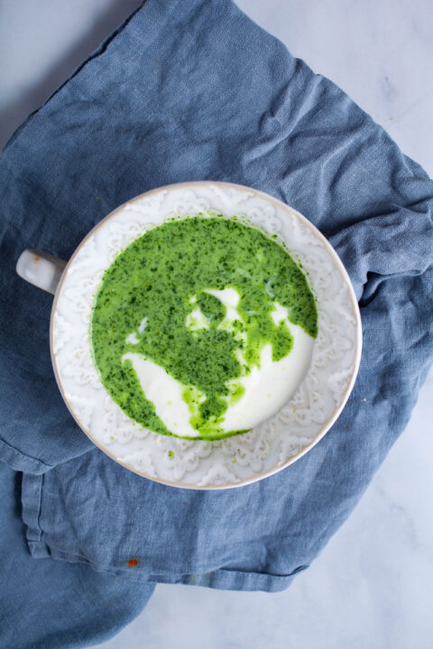 A small bowl filled with yogurt and a herbal green mixture.