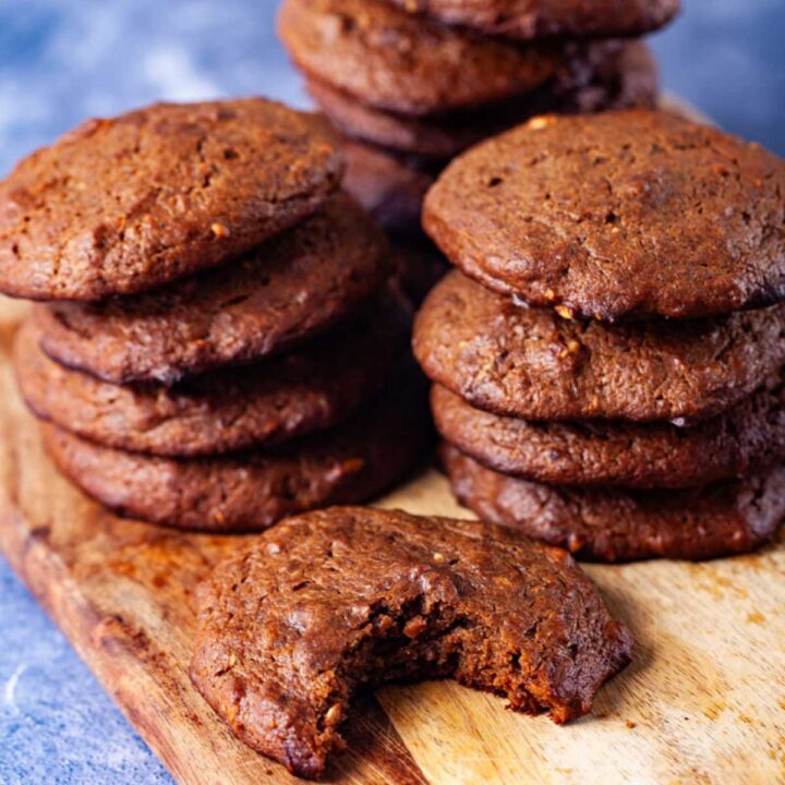 Brown baked cookies stacked on a wooden board