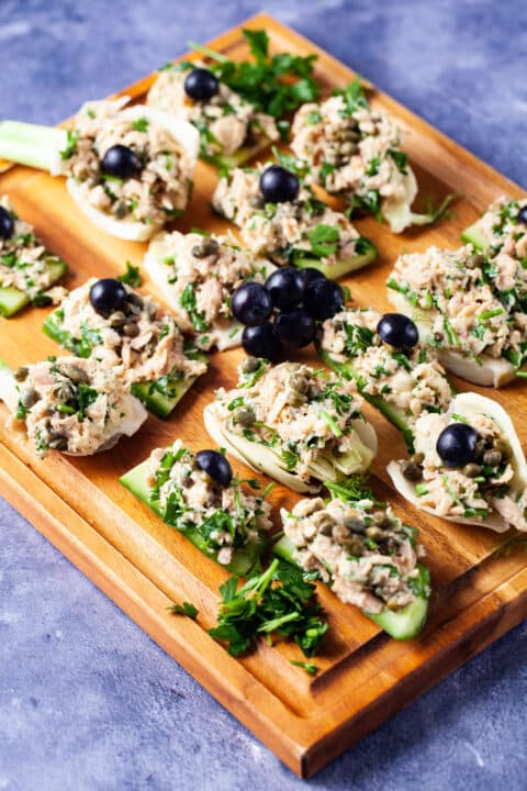 Fresh cucumber and fennel slices topped with tuna salad and garnished with dark grapes neatly presented on a wooden board.