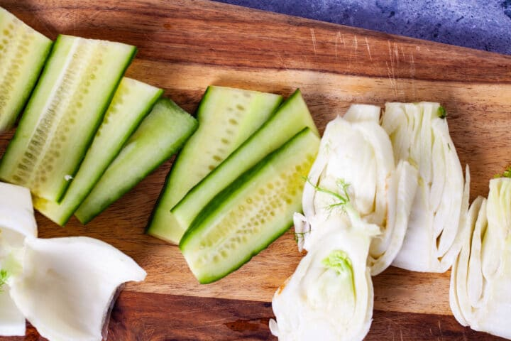Fresh cucumber and fennel slices laid out on a wooden board.