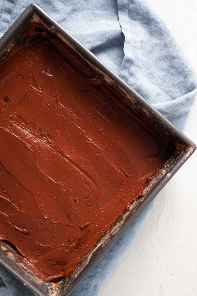 Creamy cacao batter in a baking pan to bake flourless chocolate brownies.
