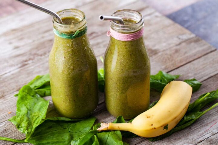 Two milk bottles filled with green juice, surrounded by half a banana and fresh spinach.