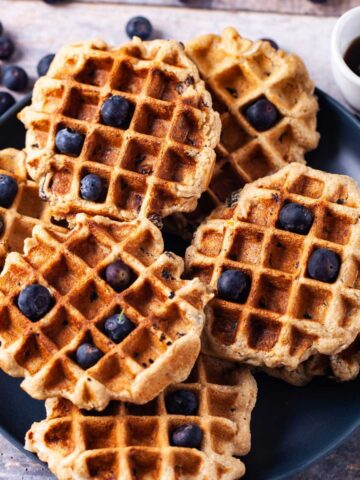 Waffles stacked on a plate topped with fresh blueberries.