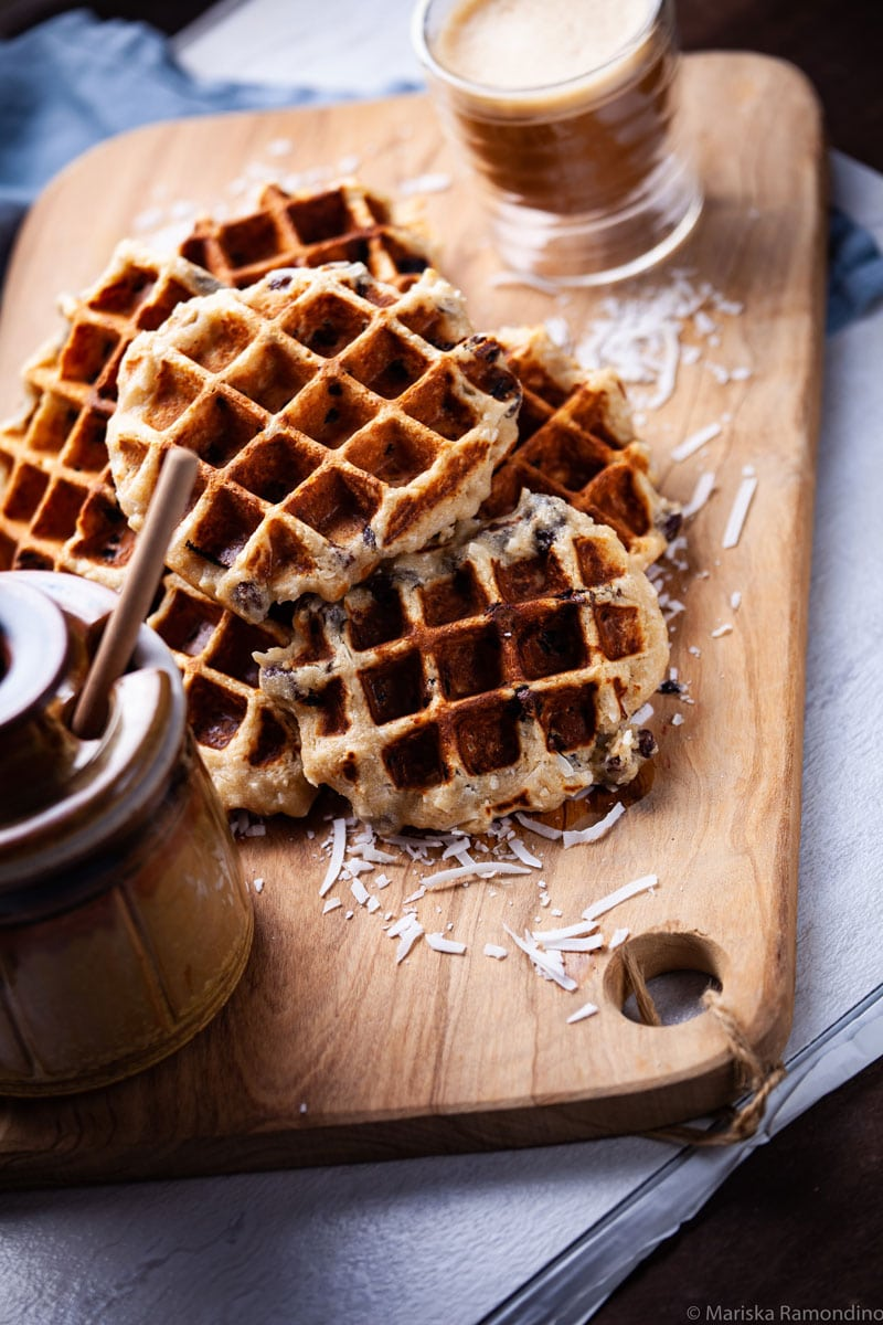 Healthy Oat waffles stacked on a wooden board served with syrup and a cup of coffee