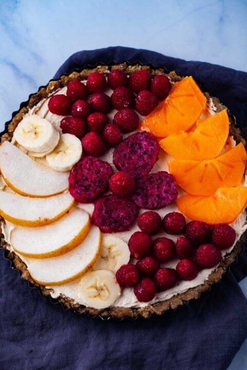 A round tart with a no bake crust, cheese filling, and topped with fruits like Asian peers, bananas, persimmon, raspberries, and red dragon fruit.